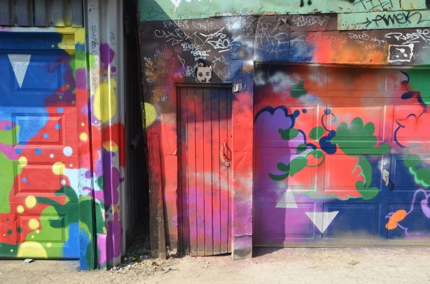 part of a garage door with a narrow wood door beside it, all covered with bright street art, abstract, mostly in red