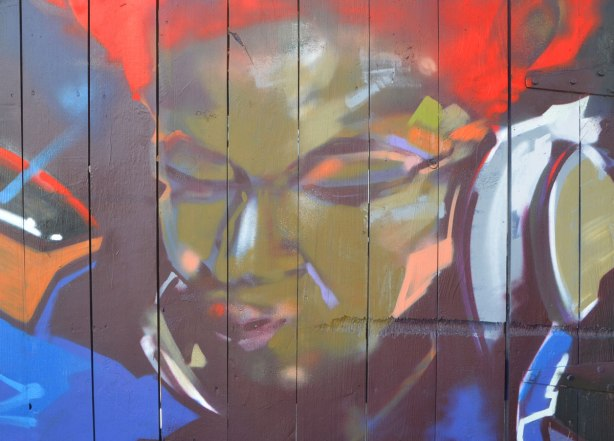 street art painting of part of a woman's face, bright red hair, greenish face, blue background, eyes closed,