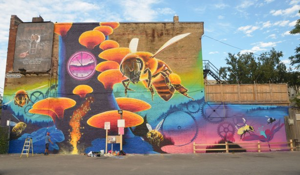 large mural, Riverside Pollinator mural, by Nick Sweetman, of a large bee, a clock, clock gears, a few small bees, a honeycomb and a flower and a very large tree
