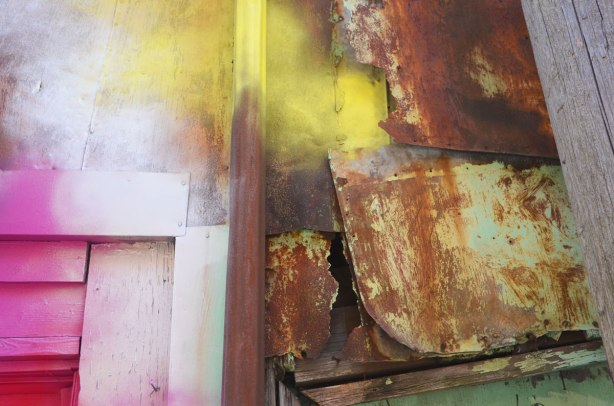 close up details of two adjoining buildings, detail of where they meet, one is old rusty metal and the other is wood that has been spray painted pink, yellow and white.