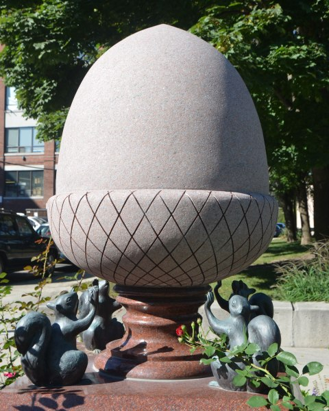 a sculpture in a park of a giant acorn with the point pointing upwards, 4 small squirrels are at the bas of the acorn trying to hold it up