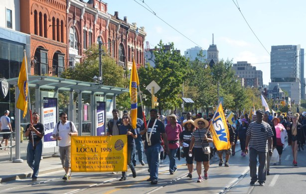 steelworkers march in a labour day parade on Queen St. West with their yellow banner