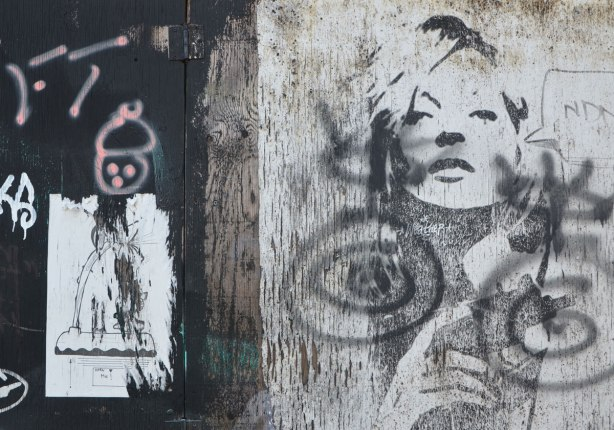 black stencil of a woman's head and hands. Also an old paper paste up of a person that is badly torn around the edges. A very simple face has been drawn above it in pink