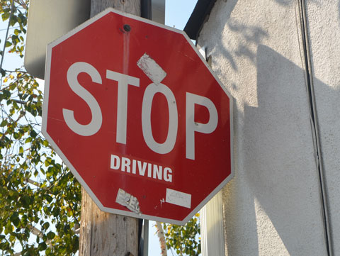 a red stop sign to which someone has stuck a sticker that says driving so now the sign says stop driving