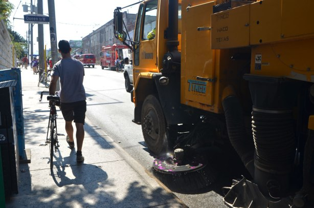 a man walks his bike on a sidewalk, walking away from the camera, a large street sweeper is right beside him as it starts to clean up the street, the last part of a parade with firemen and fire trucks is in the distance