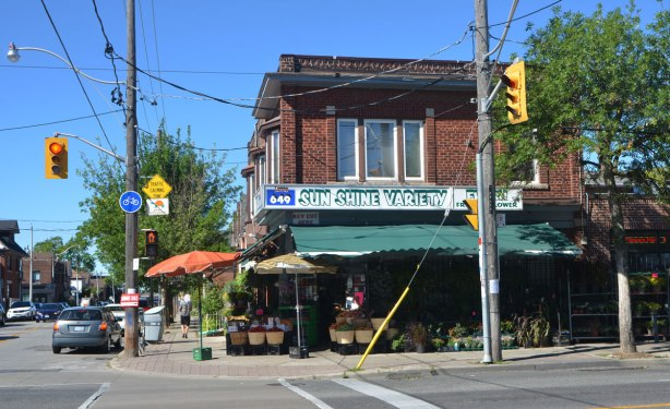 a variety store on a corner of 2 streets in a mostly residential area. Green awning on one side of the building, an orange umbrella stands over the corner. sign on store says Sunshine Variety.