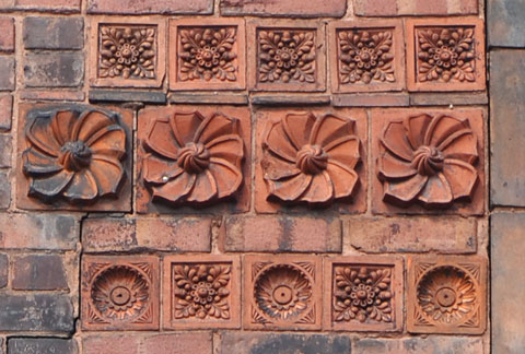 detail of house covered with terra cotta tiles with different designs on them.