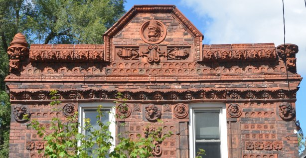 house covered with terra cotta tiles with different designs on them. upper part of front of house
