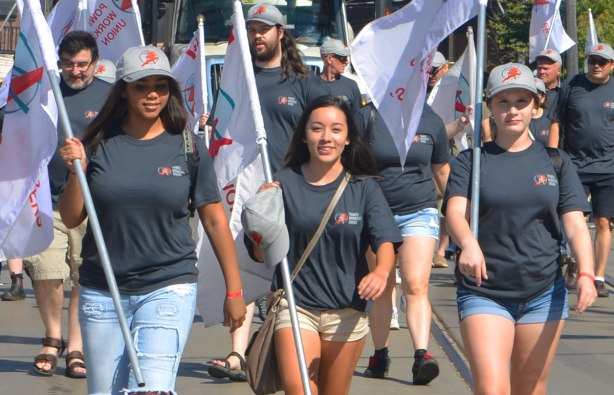 a group of people from the Power Workers Union wear grey t-shirts and and hold flags while they walk in the parade including three smiling young women at the front of the group