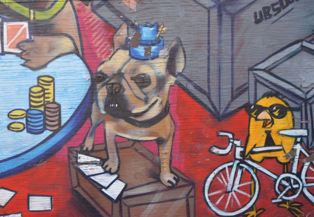 part of a Uber 5000 mural, a dog with a tiny blue hat and a yellow birdie on a bicycle