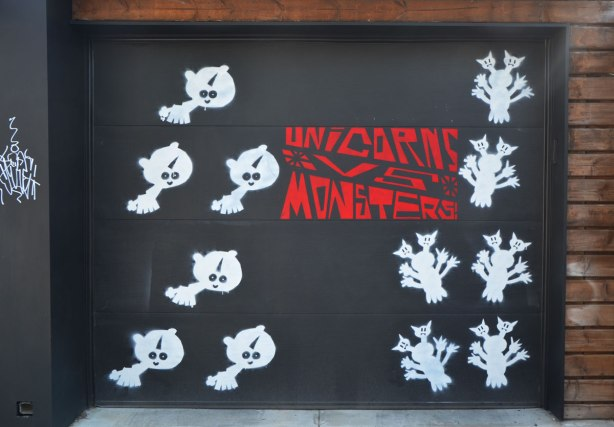 a garage door painted black with white creatures, 6 on one side of the red words Unicorns vs monsters and 6 white ones on the other side