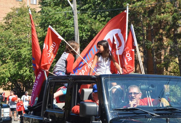 Two kids sitting in the back of a pick up truck, with red and white unifor (union) flags. Two men in the cab of the truck
