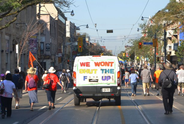 large sign covering the back of a van that says We Won't shut the f*** up, in a parade, with people walking on both of it, walking away from the camera