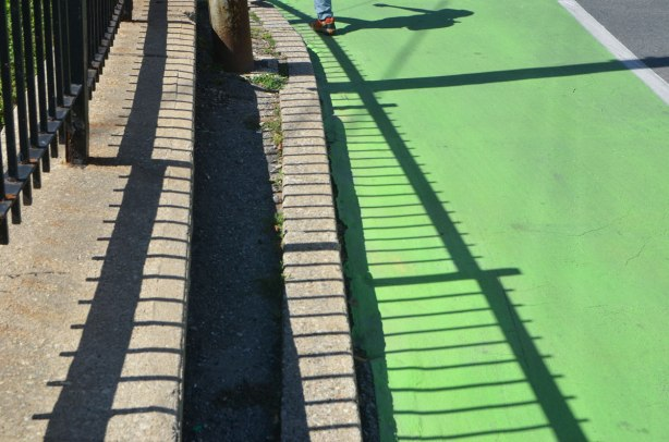 shadows of a railing along the side of a street with no sidewalk, just narrow space between the fence and the kerb, green bike lane. At the top of the photo is a shadow of a pedestrian walking, backpack on.