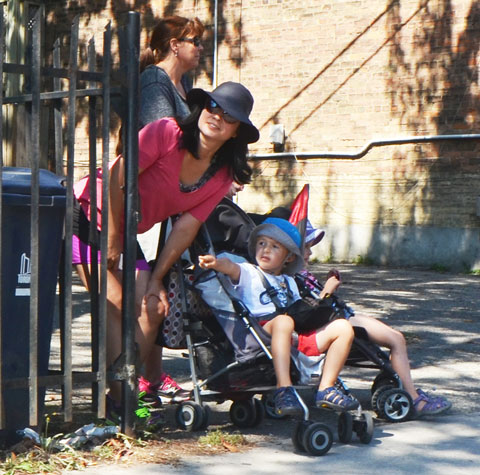 a woman in a pink top and a black wide brimmed hat leans down to talk to her son who is sitting in a stroller. He's pointing down the sidewalk. They are watching a parade go by.
