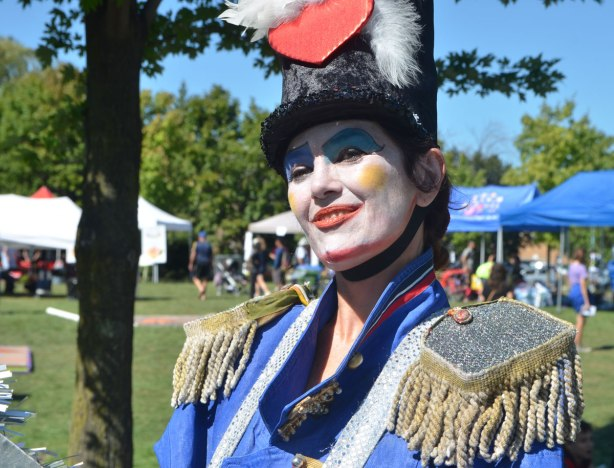 a woman white painted white face, yellow cheeks and red lips, wearing a costume in blue with padded shoulders and a fringe around the shoulders, top hat with but white feather and a big red heart