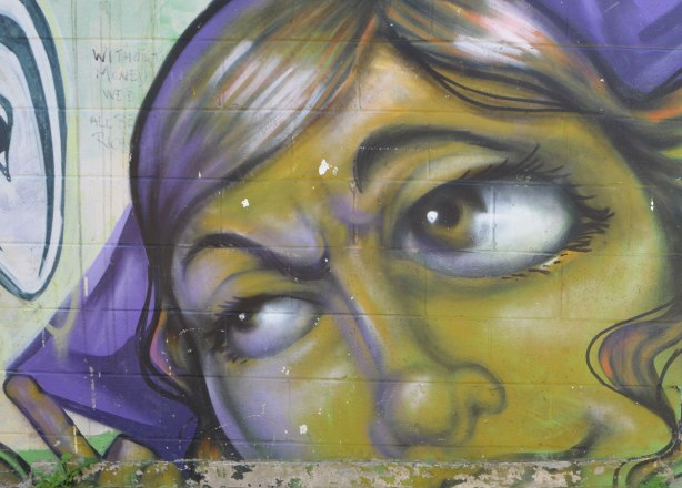 street art painting of part of a woman's face, on a wall, in greens and purples, she is looking to the left