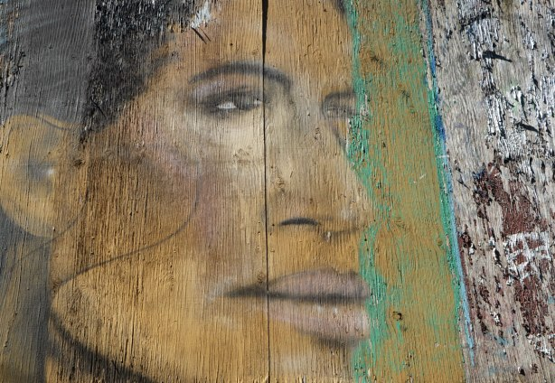 street art painting of part of a woman's face on a wooden fence, old and faded and the wood is starting to crack