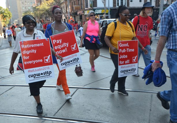 women walking in a Labour Day parade carrying placards in red background with white lettering that say, 1. Retirement dignity for everyone, 2. Pay equity now, 3. Good full-time jobs for all.