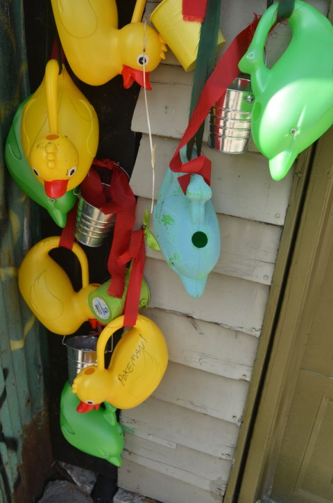 watering cans hanging along the side of a garage in an alley, many of them are in the shape of yellow rubber duckies and one is a light blue fish shape. A few are little silver coloured metal buckets.