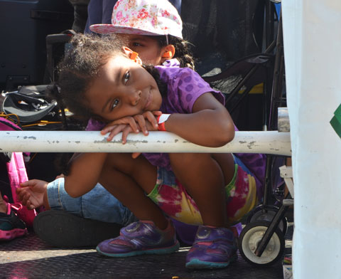 a young girl rests her arms and head on a metal railing as she rides on a float in a parade