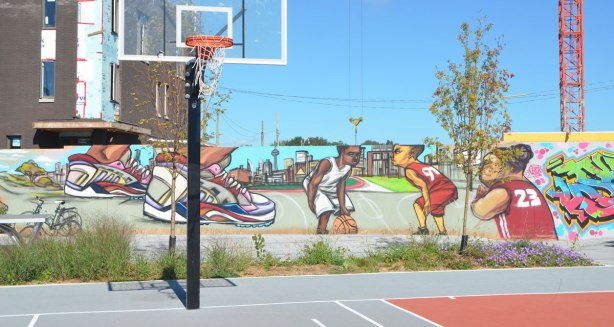 mural of basketball players playing, mural is behind a basketball court, also mural of close up of players feet with running shoes on