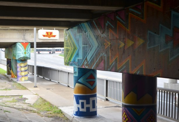 geometric designs in a mural on concrete pillars on an underpass, by a TTC subway station