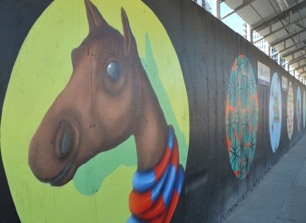 large circle on black wooded construction hoardings.  In the circle, painted light green is a brown horse head and neck, with a red and blue striped scarf around its neck, painted by birdo