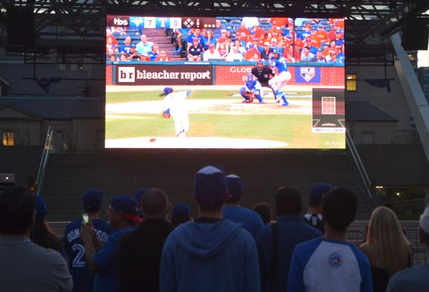 people watching the Blue Jays baseball team playing a game on a large TV screen outside.