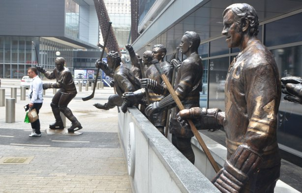 statues of hockey players lined up behind the boards as if they were in a rink, some of the players in the background are jumping over the boards. Number 14 for the Toronto Maple Leafs is in the foreground, Dave Keon.
