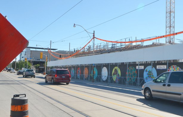 A street, Dundas East, with construction hoardings painted with street art pictures inside large circles ona black background, cranes in the background. A couple of cars