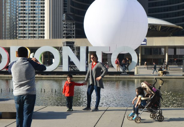 a man is taking a picture of his wife and young son in front of the water and 3D toronto sign in Nathan Phillips Square, a girl in a stroller watches.