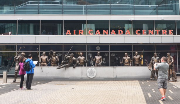 line of statues of hockey players in front of the Air Canada Centre, Legends Row in Toronto, a few people are standing in front of the statues.