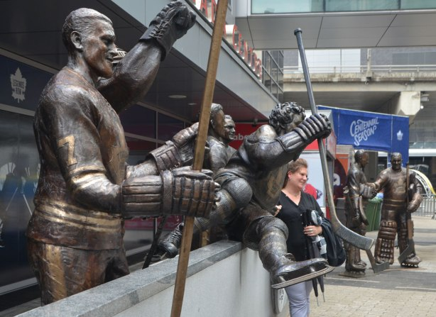 a woman poses for a photo with a line of statues of hockey players