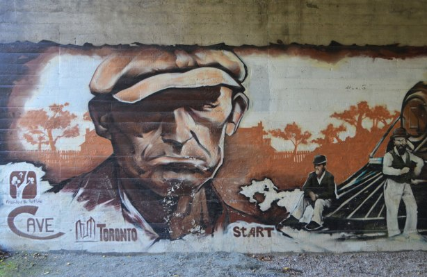 part of a mural under a bridge on the Beltline path, by StART, in brown tones of the hhistory of the railroad in the area (scenes from), an older man in a brown cap