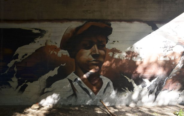 part of a mural under a bridge on the Beltline path, by StART, in brown tones of the hhistory of the railroad in the area (scenes from) a young man in a brown cap