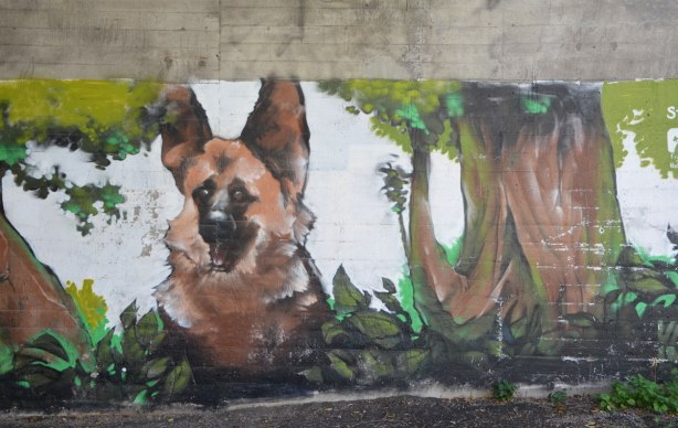 part of a mural under a bridge on the Beltline path, by StART, of nature scenes, a large dog is sitting beside a tree