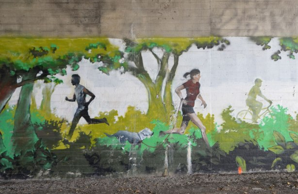 part of a mural under a bridge on the Beltline path, by StART, people walking on a path through the woods including a jogger, a woman walking a dog, and a cyclist.