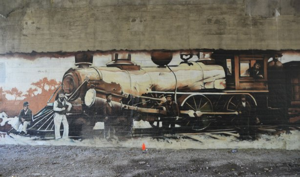 part of a mural under a bridge on the Beltline path, by StART, in brown tones of the hhistory of the railroad in the area (scenes from), a large locomotive with a man standing by the front of it.
