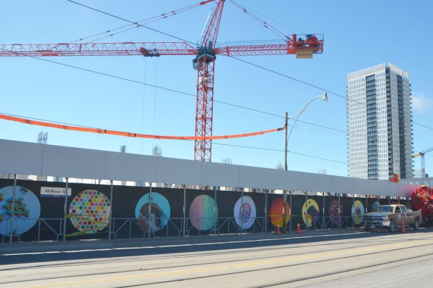 A street, Dundas East, with construction hoardings painted with street art pictures inside large circles ona black background, cranes in the background.