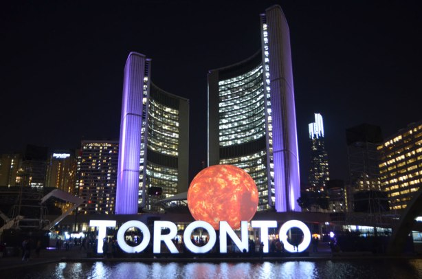 the 3D toronto sign lit up in white, city hall behind it in purple lights, and a large globe representing the sun glows orange as part of an art installation, night time photo.