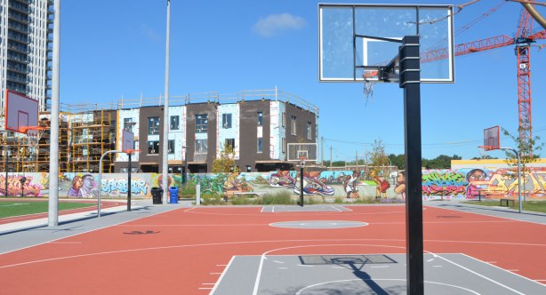 outdoor basketball court, with a mural in the background, and construction beyond that.