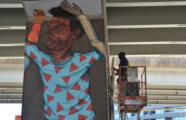 a man stands on a lift as he paints a mural, in the foreground is a man in a shirt with red triangles all over it that has already been painted.
