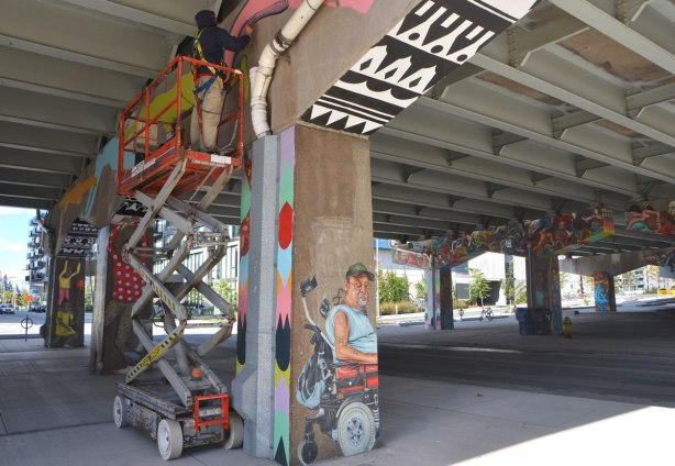 a street artist (Troy Lovegates) is on a lift and painting a mural on the concrete supports on an underpass. Other supports are in the picture, they have already been painted.