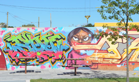 mural of a woman, and some text, on a fence behind some outdoor picnic tables