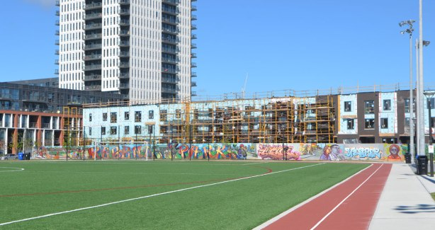 green soccer field and clay track in the foreground, small trees and a mural along the end of the field, new apartments being constructed in the background.
