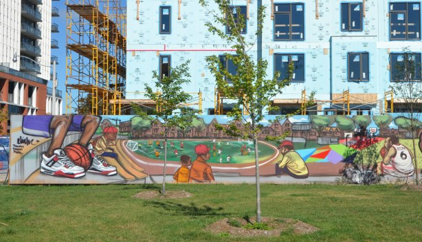 mural by elicser elliott on a fence between grassy field and new apartments being built, people watching a soccer game, a person sits on a bench with a basketball between their feet.