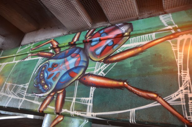 part of a mural, a large blue and red spider with orange legs, on a verylarge spider web