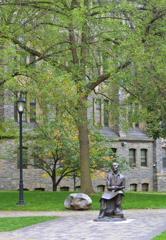 a statue of a man sitting is beside a rock and a light post, they are in front of a large tree and an old stone building, on the University of Toronto campus.