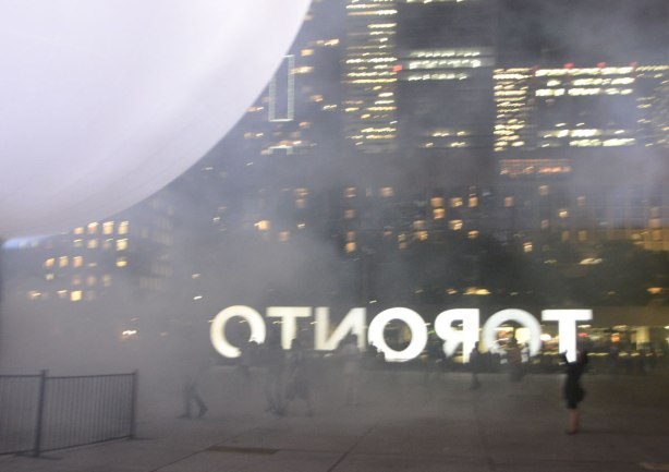 large white globe lets off steam or fog in Nathan Phillips square.